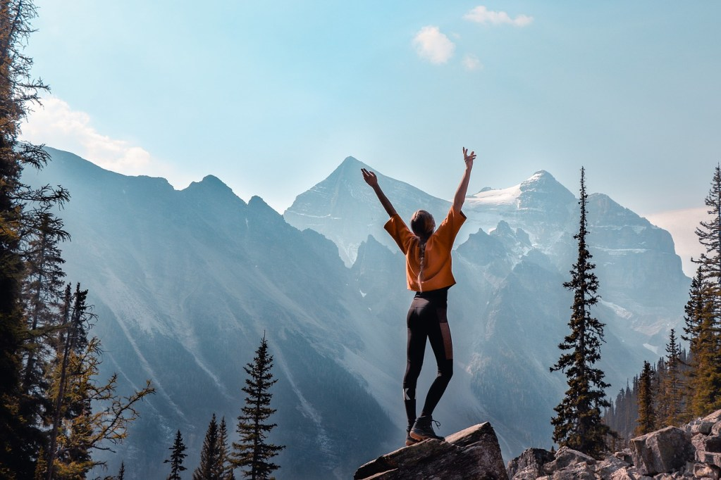 Une femme en montagne , levant les bras vers le ciel