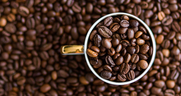 Overhead view of a measuring cup filled with whole coffee beans sitting atop a large pile of coffee beans