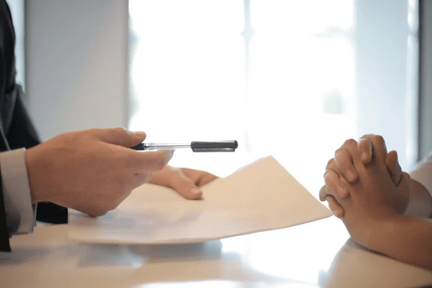 The hands of two people talking across a desk.