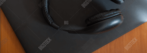 black laptop on wood surface with black hearphones