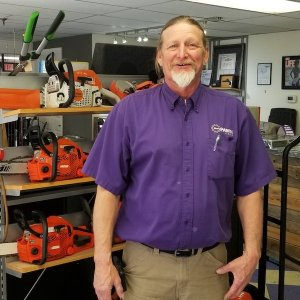 man with gray beard purple shirt smiling chain saws in background