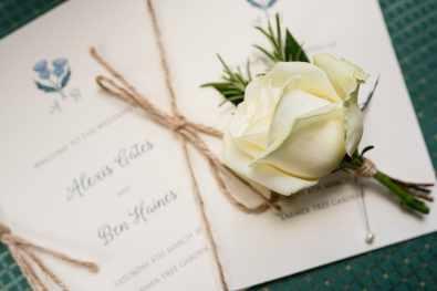 Rose rests on the wedding stationery - Larmertree Gardens wedding