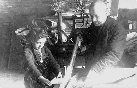 Az idős férfinak egy gyermek segít papír ívek vágásában egy lodzi papír üzemben.