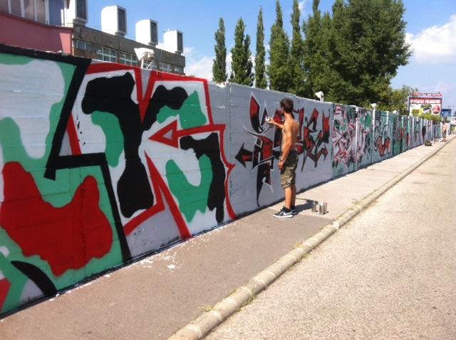 Belini fal a Szigetnél. - OOPS Partizán Street Session Abból, ahogy mesélsz, úgy tűnik, elég korán kezdted…  '94 óta foglalkozom a graffitivel, akkor voltam tíz éves. Vidéken éltünk, egy paneltömbben. Egyik nap lementem az utcára és láttam, hogy éppen festik a falat a házunkkal szemben. És megkérdeztem: ti meg mit csináltok? Ilyen egyszerűen jött. Így kezdtem el rajzolgatni, valamennyit graffitiztem is egy barátommal, de akkor még nem volt internet. Kisgyerekként tapogatóztam csak a sötétben, egyáltalán nem tudtam hova kötni a dolgokat. Ez az eset volt egyébként Magyarország első graffiti jam-je, az, aki az egészet szervezte pedig a későbbi rajztanárom. Ezek az arcok állnak itt a falnál most negyven évesen is. Fontos, hogy itt nem arról van szó, hogy kis hülyegyerekek idejönnek, aztán firkálnak valamit a falra.  Téged kerestek meg az OOPS ötletével, hogy gyűjtsd össze a művészeket. Kiket hívtál, mi alapján válogattál? Ha jól tudom, az itt lévők fele képzőművész, fele graffitis…  Amikor Pátkai Marci megkeresett, azt kérte, hogy ne kimondottan graffiti jam-et csináljunk. Legyen inkább street art, művészi impulzusokkal feltöltött embereket válogassak össze. Próbáltam egy határhelyzetet kialakítani. Legyenek olyan graffitisek, akik képzőművészettel is foglalkoznak és legyenek művészek, akiknek eddig még ilyesmihez nem volt közük, most fújnak először. Ettől végül olyan hatása lett annak, amit csináltunk, mint egy kis berlini fal. Megjelenik rajta egyrészt egy naiv graffiti világ, de van száraz ecsettechnika is, kenős festék, fújós festék. Van, aki karaktervilágot használ, a másik pedig betűket, vagy éppen mind a kettőt. Teljesen különböző világok és technikák ötvözete jelenik meg százharminc méteren. Azt is fontosnak gondoltam, hogy többféle korosztályból hívjak embereket. Jöjjön a fiatal generáció, dolgozzon együtt az idősebbekkel, nekik ez egy nagyon jó platform. Önbizalmat ad, inspirál, ha fiatalként elfogad egy ilyen közeg.