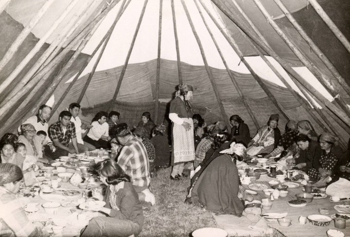 Large_group_of_people_eating_a_meal_inside_a_tipi