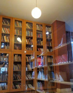 ράφια με βιβλία που αντανακλώνται στα τζάμια της βιβλιοθήκης