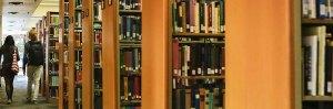 Two students walking through stacks