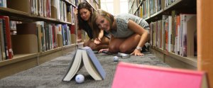Two students watch a golf ball roll under a book in the library