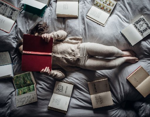 figure lies flat on a bed holding a book up to her face, surrounded by books in the shape of a circle