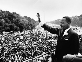 black and white image of Martin Luther King Jr waves to a crowd assembled on the National Mall in Washington, D.C.