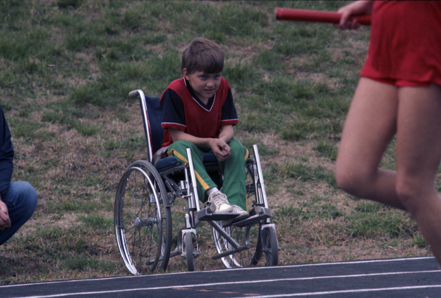 wheelchair olympics folding directors chair young boy in watches a runner texas disability history