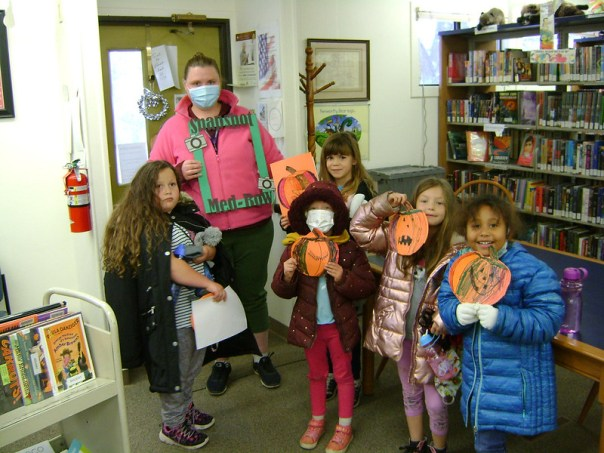 Woman with group of children standing in library. Children are holding up pumpkins made from construction paper.