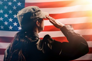 Silhouette of a female soldier saluting against the background of the American flag.