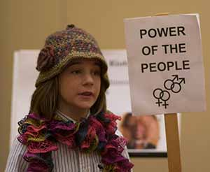 "Young History Day participant in hat holding ""Power of the People"" sign"