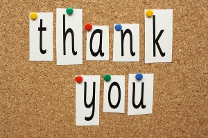 The phrase Thank You in cut out letters pinned to a cork notice board
