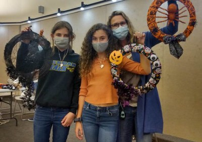 Three women wearing face masks and holding handmade wreaths. At least two appear to be teens.