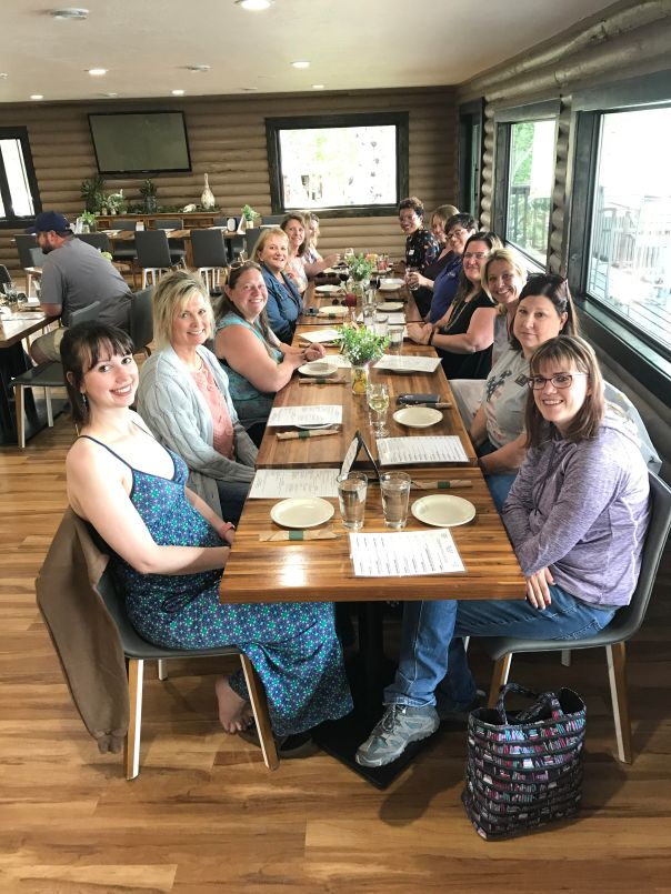 13 women sit at a long restaurant dining table, smiling at the camera.