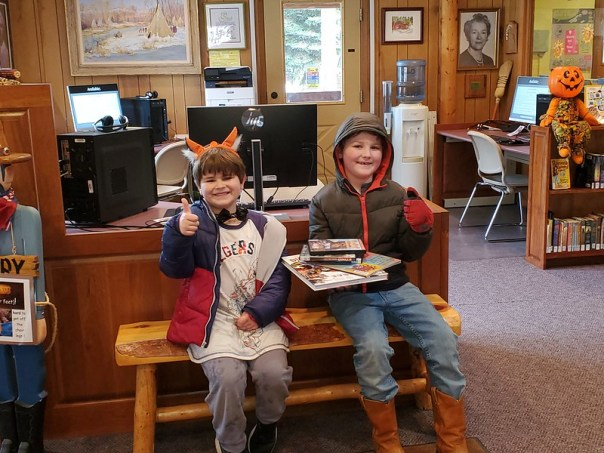 Two boys sitting on bench showing off library books and videos and giving thumbs up signs.