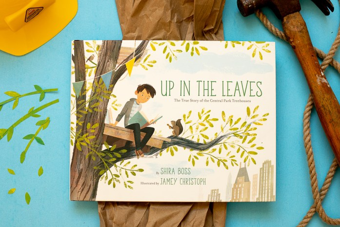 The picture book, Up In The Leaves by Shira Boss and Jamey Christoph, is in the center of this image. A hammer, rope, hard hat, collage stems and leaves and brown paper surround the book.