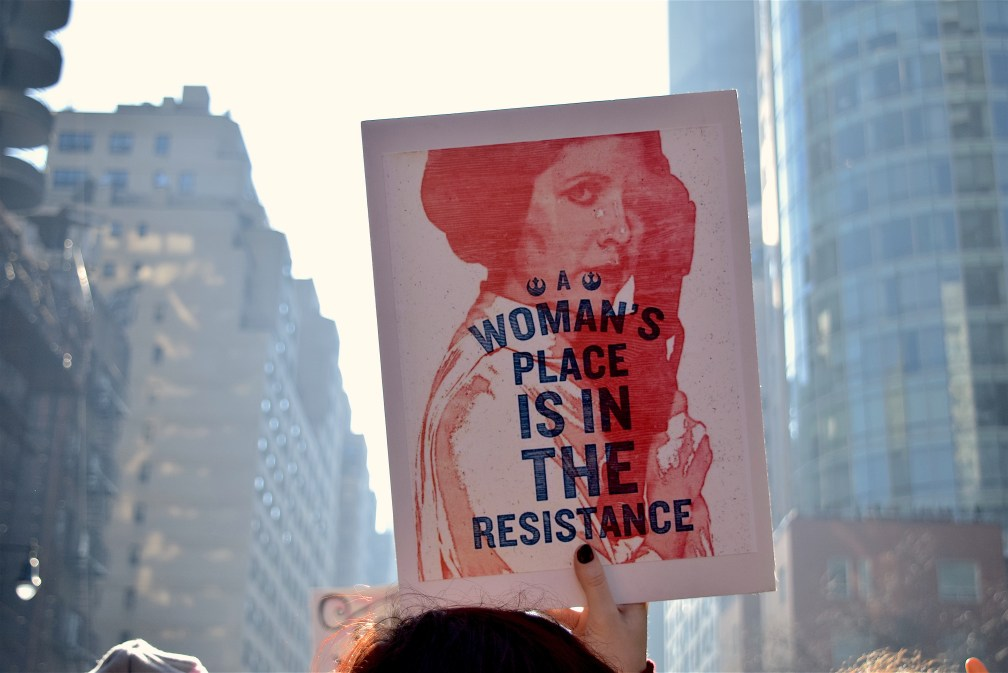 "rally poster with Princess Leia with text ""Woman's Place is in the Resistance"" overlaid"