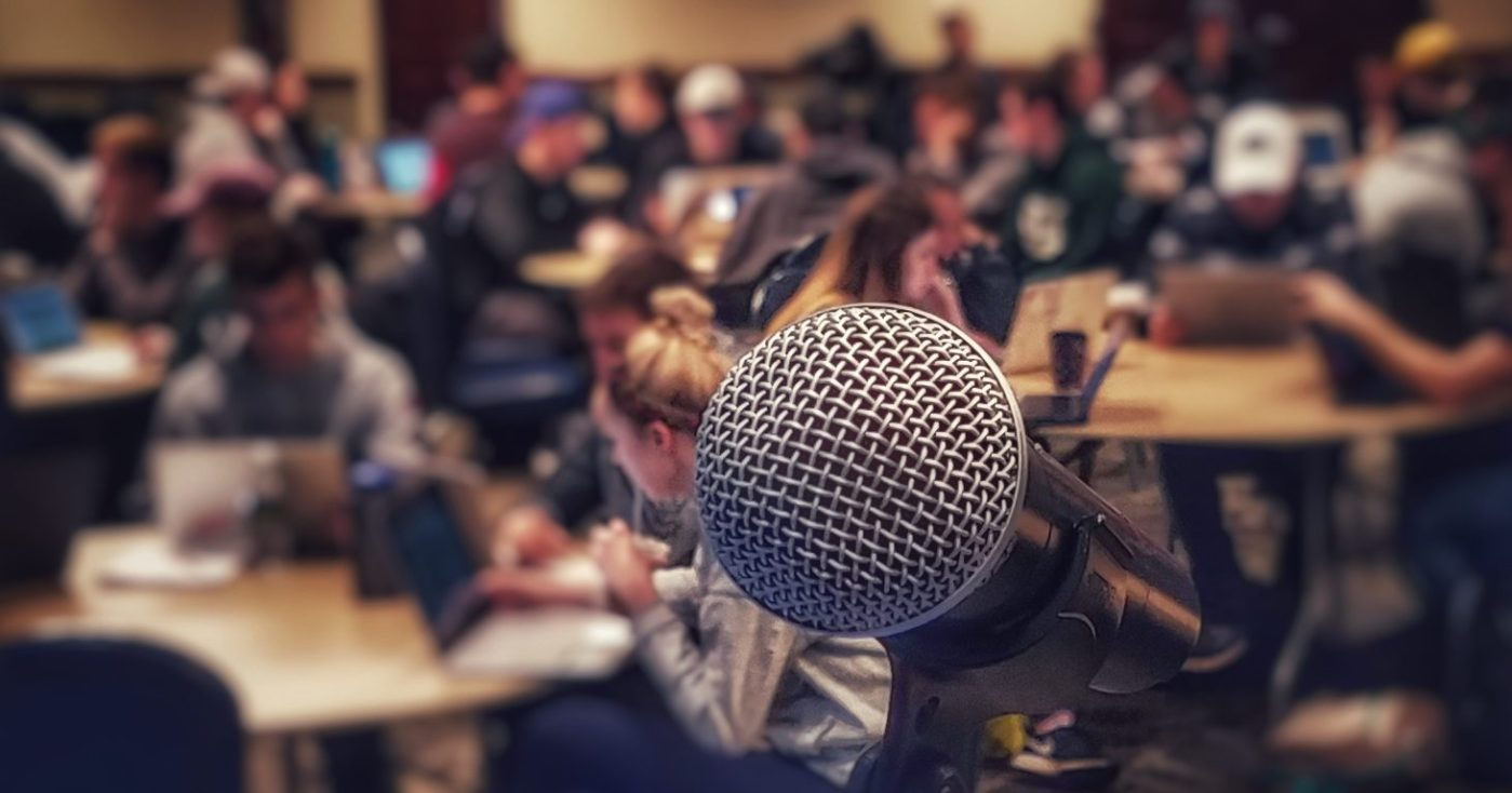 a microphone at a podium in front of a classroom of students