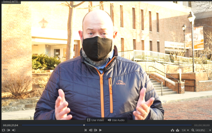 A screenshot of a video frame of the author, shot outside, in front of the library.