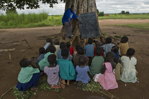 a teacher, outdoors, providing a lesson to a group of children