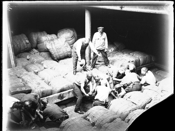 Workers packing Australian wool into a cargo ship