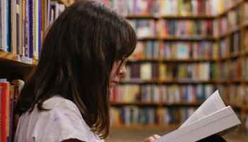Joven leyendo libro en biblioteca