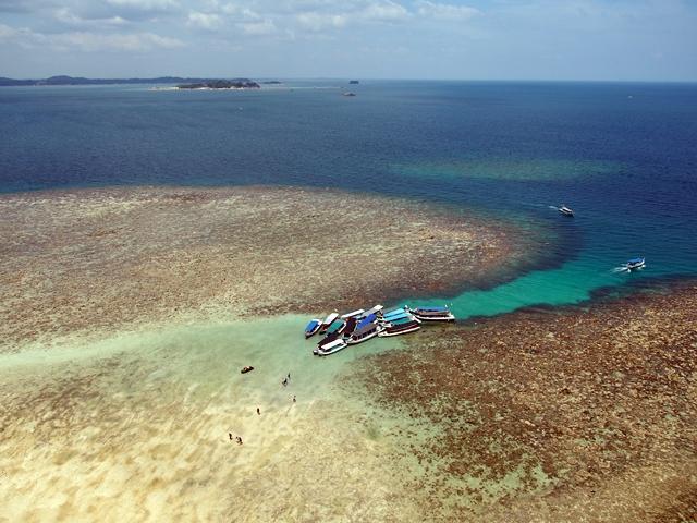 kecantikan warna biru laut berpadu harmonis bersama beberapa perahu yang bersandar