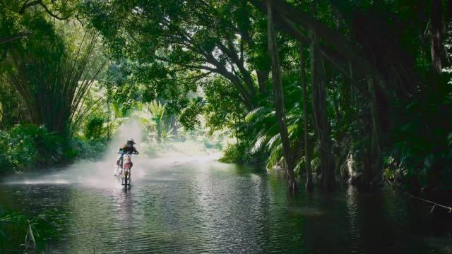 Robbie Maddisons melewati sebuah sungai dengan sepeda motor.