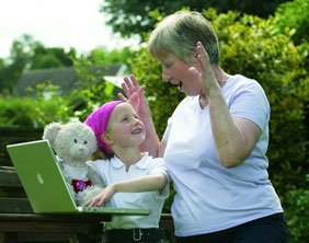 Rhiannon Stone shows her nan Mary Price the new website with the help of her teddy bear Pinky