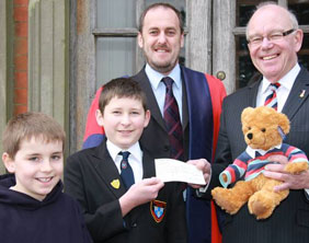Jack Gayton, James Dance and Dr Daryl Brown present the cheque to Jeremy Hobbs and Hero bear