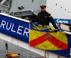 Captain Shaun Jones takes the Staffordshire Flag aboard RFA Wave Ruler