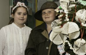 Kate Cotton as a land girl and Oliver Grigg as a solider in front of their Christmas tree