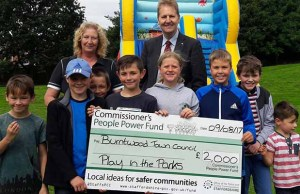 Heather Tranter and young visitors to a Play in the Parks event receive the funding cheque from Crime Commissioner Matthew Ellis