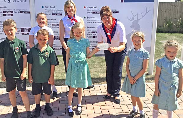 The cheque is presented to pupils from Henry Chadwick Primary School