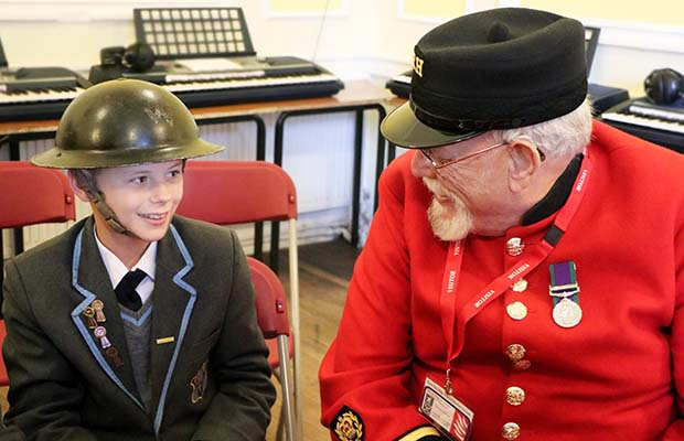 A Chelsea Pensioner talking to a student at Maple Hayes