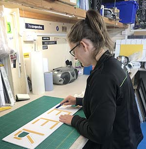 Sophie Mead preparing signage for a Central England Co-op project