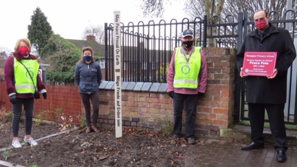 A Peace Pole being planted as part of the pilot project in Warwickshire