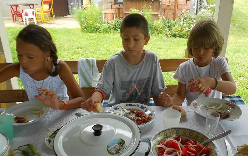 deca sede za stolom i ručaju