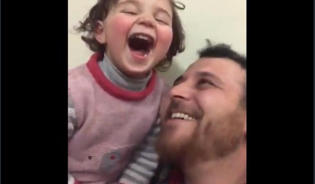Padre sirio enseña a su hija a reírse, en medio de un bombardeo ruso