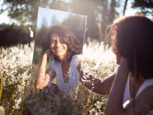 Une femme souriante devant son miroir