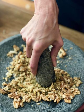 pounding walnuts in morter and pestle