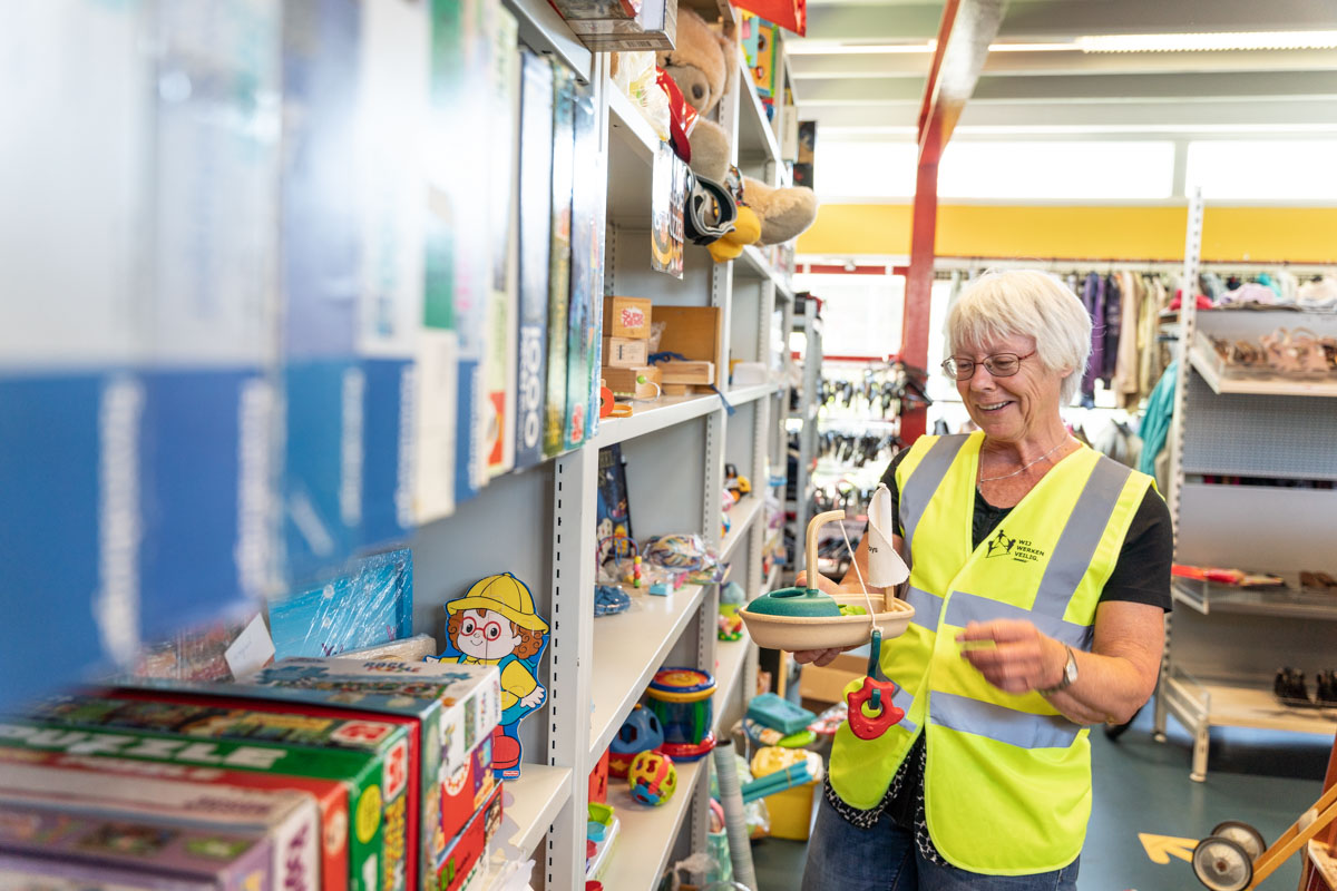 vrijwilliger blij spullen bootje ruilwinkel fotografie
