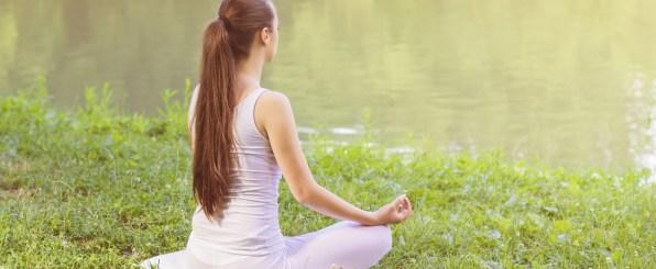 湖畔で瞑想する女性