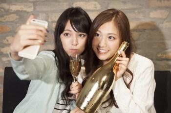 ワインのボトルを持って自撮りする女性たち