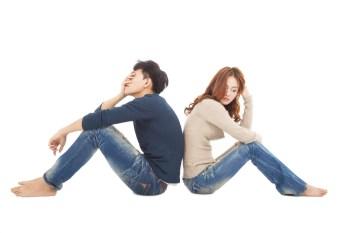 背中を向き合って座るカップル
