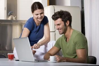 パソコンを見て話し合うカップル