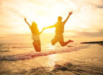 海辺でジャンプするカップル